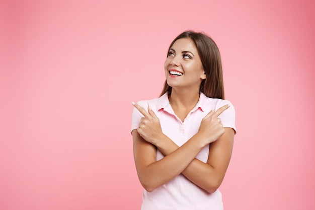 Menina sorridente no sportswear rosa, olhando para longe com as mãos do outro lado