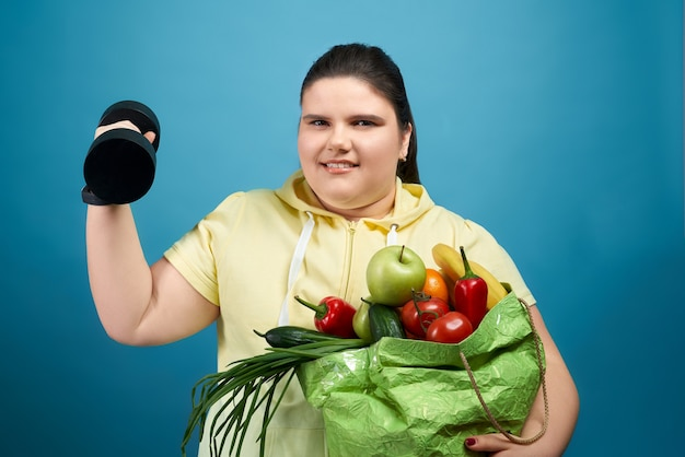 Menina sorridente no suéter amarelo, olhando para a câmera e mantendo o pacote com frutas e vegetais em uma mão e halteres na outra.
