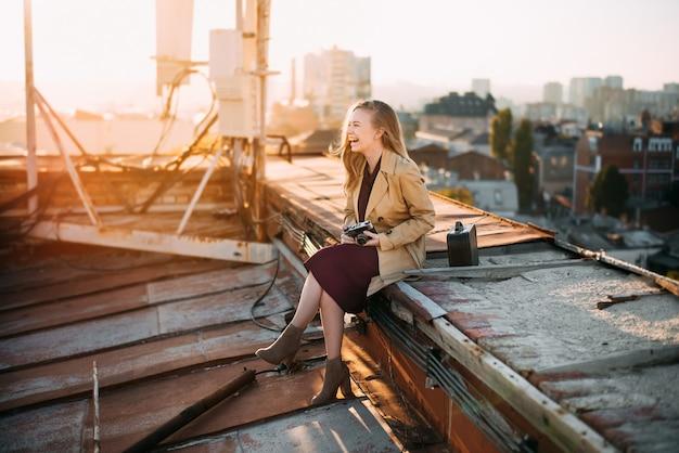 Menina sorridente no telhado com a câmera jovem loira posando ao pôr do sol