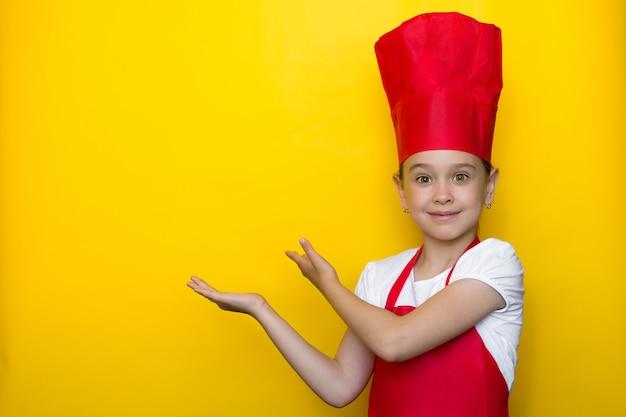 Menina sorridente no terno de um chef vermelho aponta com as duas mãos para um copyspace