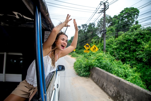 Menina sorridente olha pela janela de um táxi, tuk-tuk