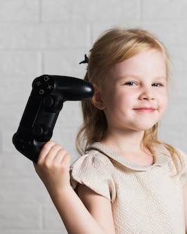 Menina sorridente, olhando para a câmera e segurando o joystick