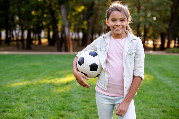 Menina sorridente, olhando para a câmera e segurando uma bola
