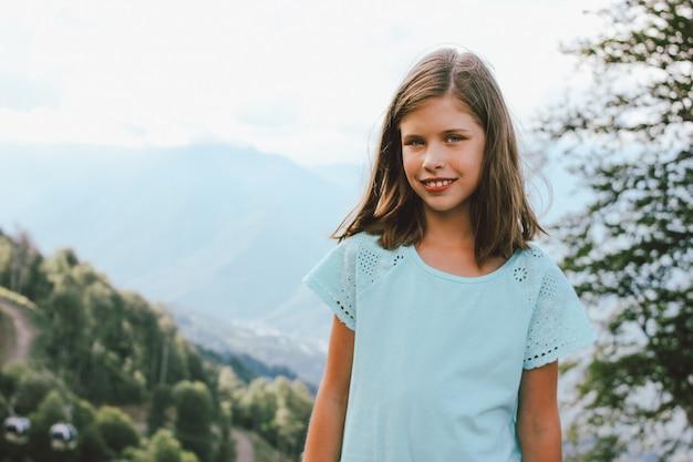 Menina sorridente, olhando para a câmera no fundo de belas montanhas