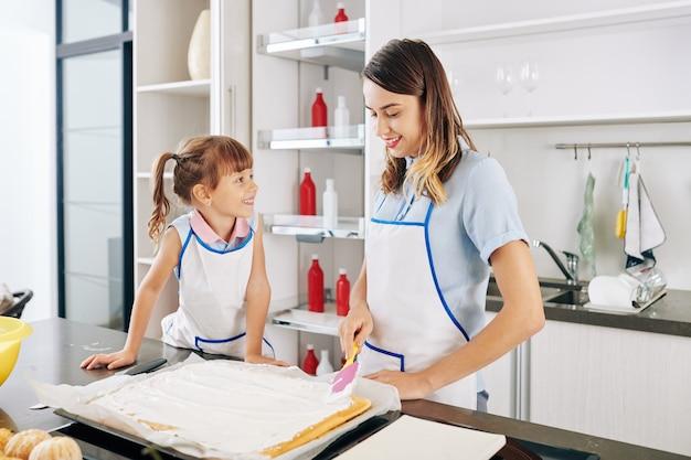 Menina sorridente, olhando para a mãe cobrindo o bolo com uma deliciosa cobertura de creme