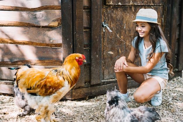 Menina sorridente, olhando para as galinhas na fazenda
