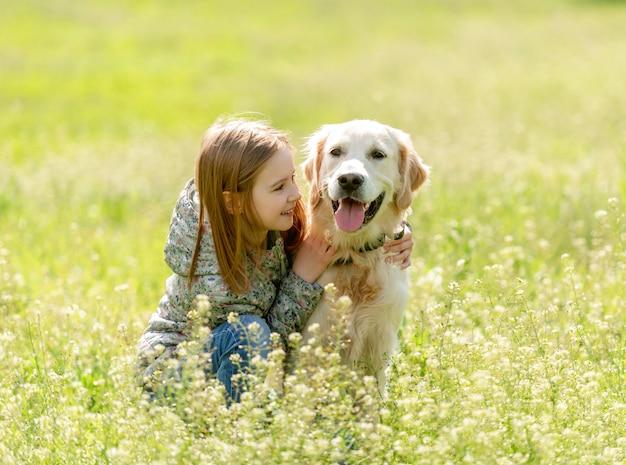 Menina sorridente, olhando para o cachorro fofo