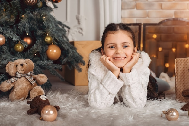 Menina sorridente perto de árvore de natal