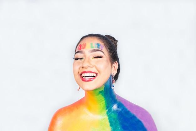Menina sorridente pintada com as cores do arco-íris com a palavra qualidade escrita na testa