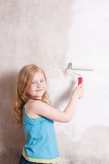 Menina sorridente pintando a parede