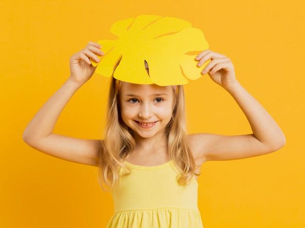 Menina sorridente posando com folha