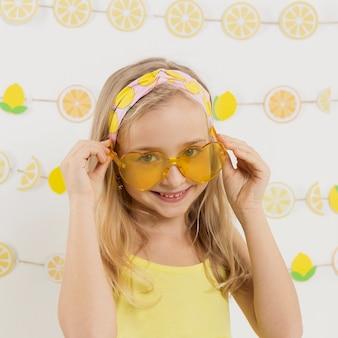 Menina sorridente posando com óculos de sol