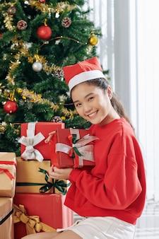 Menina sorridente posando com presente