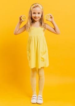 Menina sorridente posando com rodelas de limão
