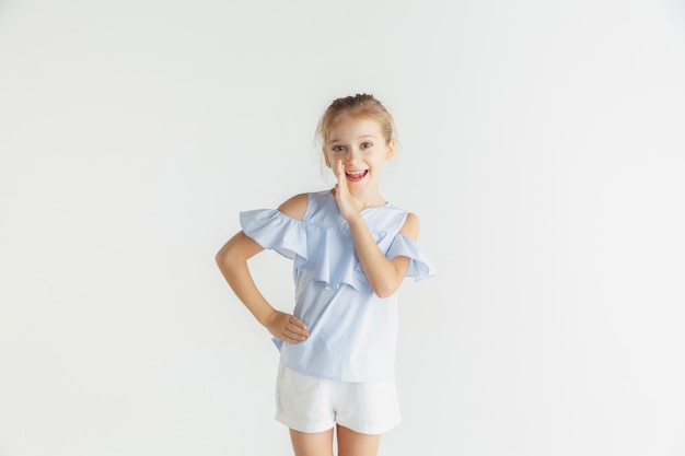 Menina sorridente posando com roupas casuais em estúdio branco
