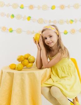 Menina sorridente posando com um limão
