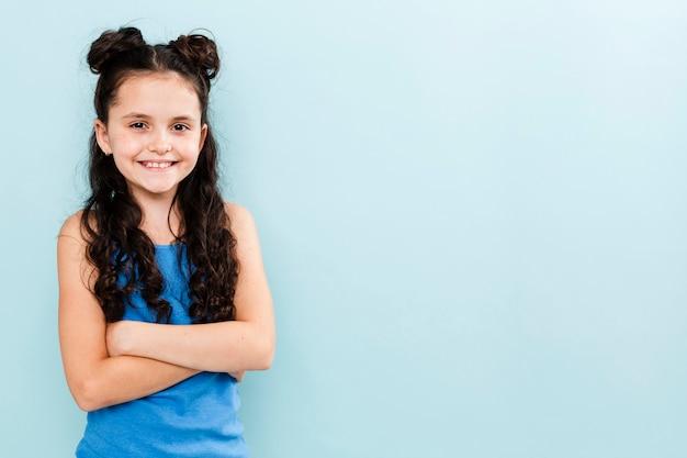 Menina sorridente posando em fundo azul