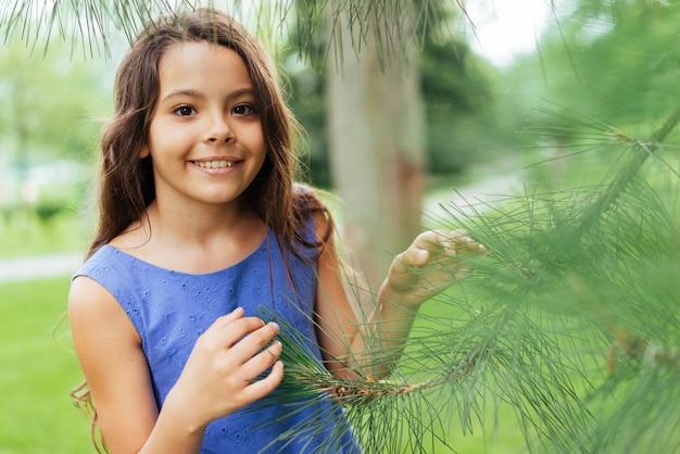 Menina sorridente posando na natureza
