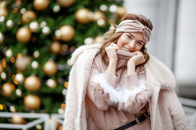 Menina sorridente posando na rua com abeto decorado turva