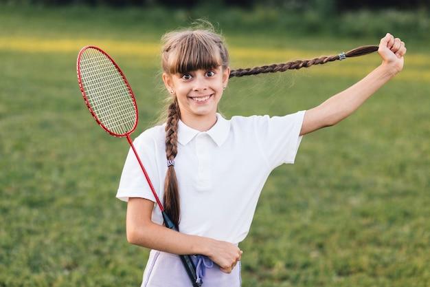 Menina sorridente, puxando, dela, longo, cabelo trançado, segurando, badminton