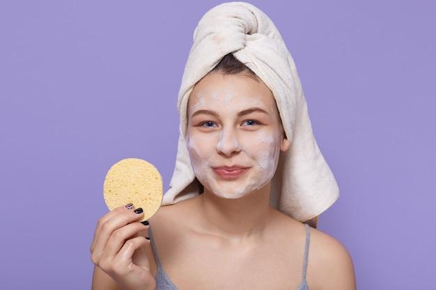 Menina sorridente saudável com a pele clara, segurando a esponja bege, usando toalha branca