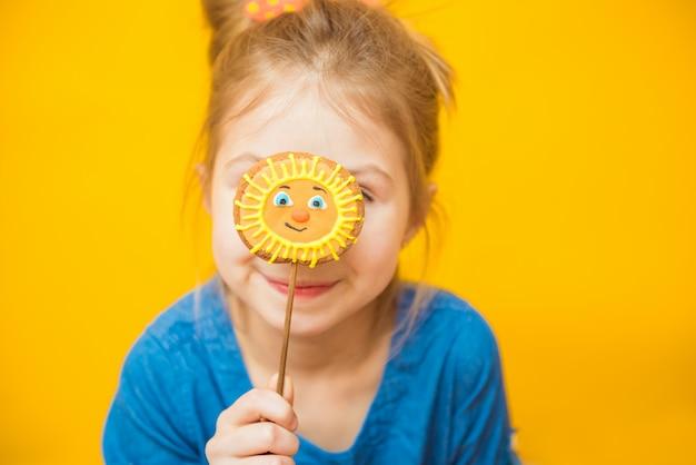 Menina sorridente, se escondendo atrás de um pão de gengibre em forma de um sol amarelo
