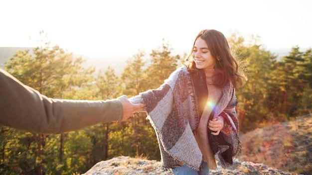 Menina sorridente, segurando a mão do namorado dela