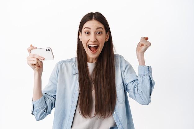 Menina sorridente segurando a posição horizontal do smartphone, vencendo no videogame, assistindo streaming de vídeo online e comemorando a vitória, boas notícias, em pé sobre a parede branca