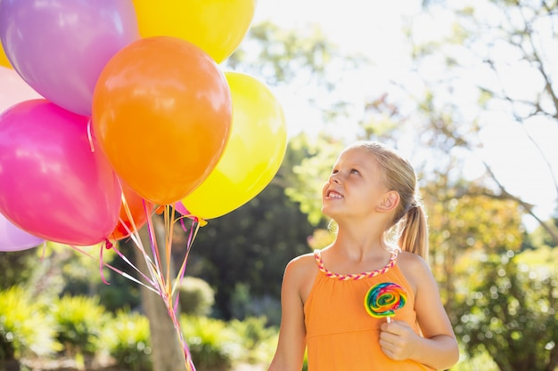 Menina sorridente segurando balões e pirulito no parque