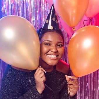 Menina sorridente segurando balões