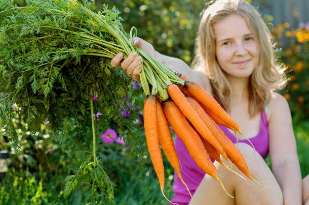 Menina sorridente segurando bando de cenouras.