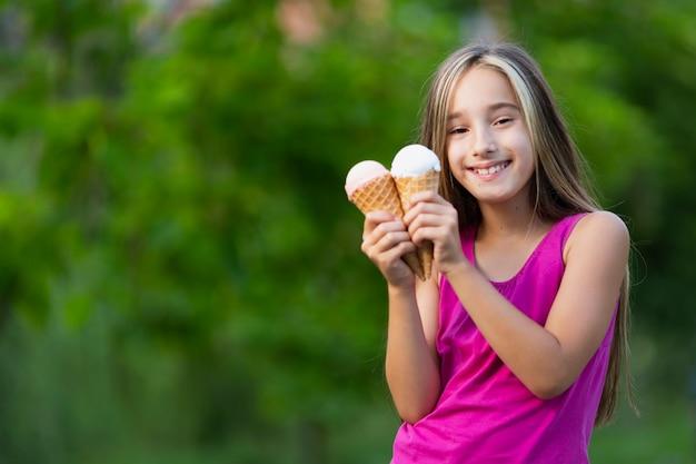 Menina sorridente segurando casquinhas de sorvete