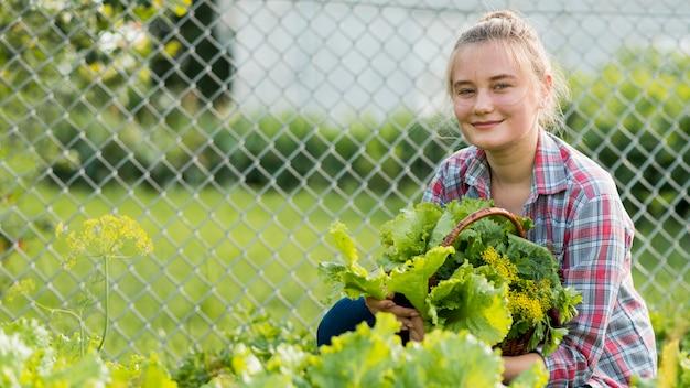 Menina sorridente segurando cesta de alface
