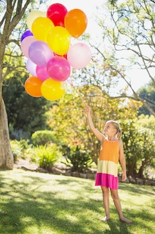 Menina sorridente segurando com balões no parque