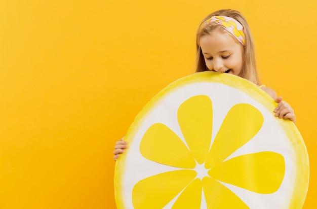 Menina sorridente segurando decoração fatia de limão
