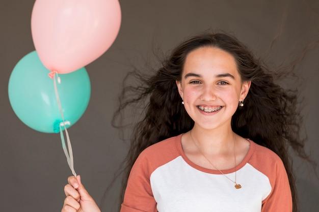 Menina sorridente segurando dois balões