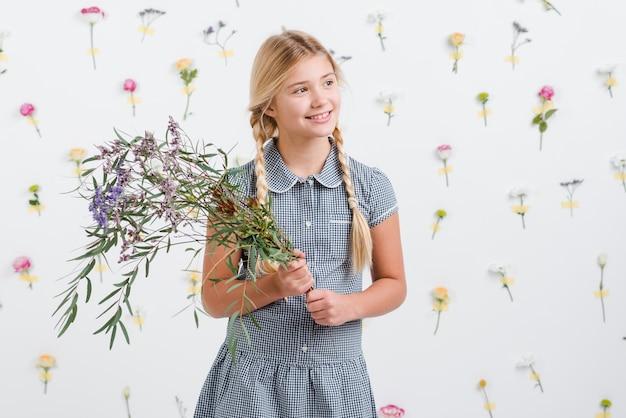 Menina sorridente segurando o buquê de flores