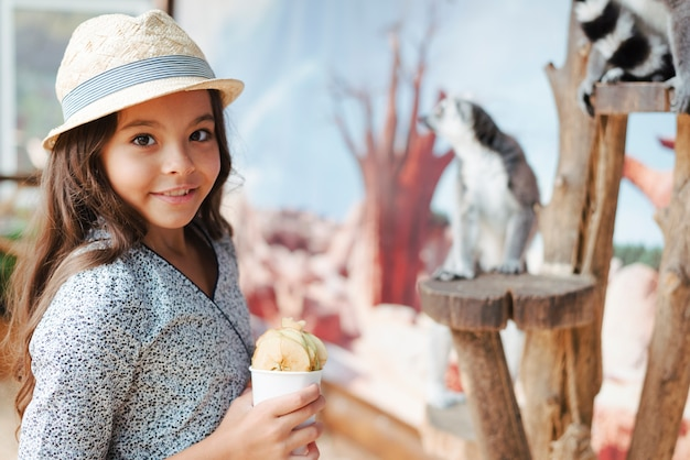 Menina sorridente segurando o copo de fatias de maçã no zoológico