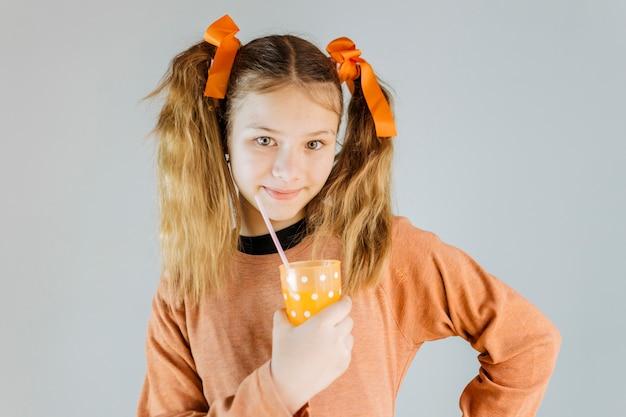 Menina sorridente segurando o copo de suco no fundo cinza