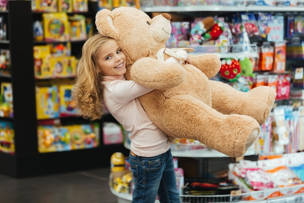 Menina sorridente segurando o grande urso de pelúcia