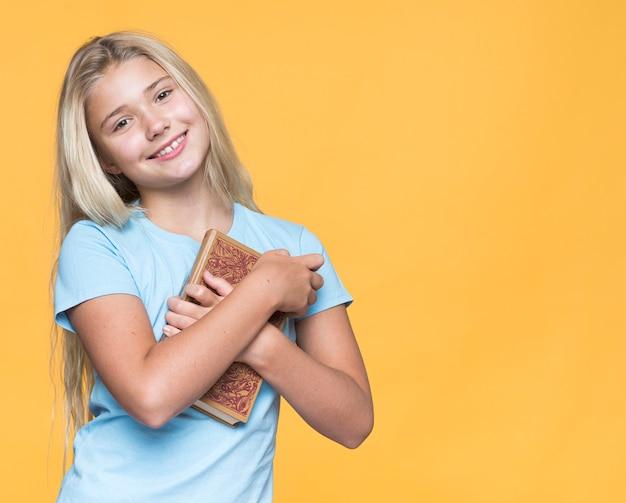 Menina sorridente segurando o livro