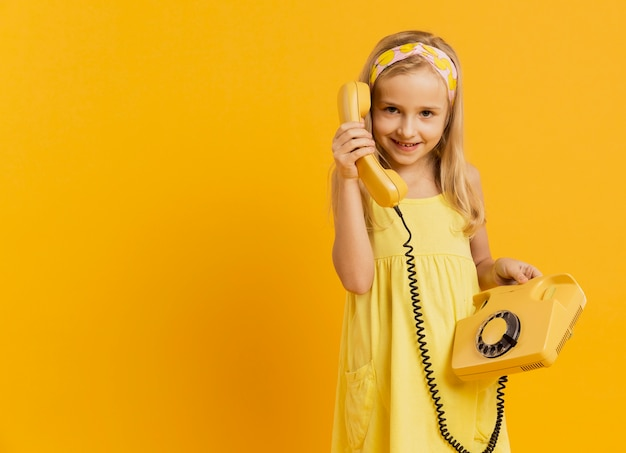 Menina sorridente, segurando o telefone com espaço de cópia
