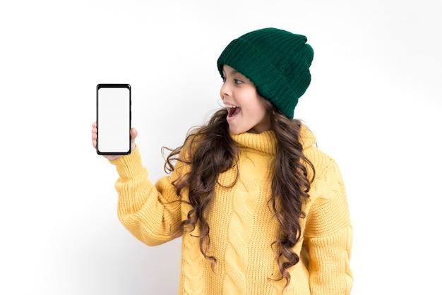Menina sorridente, segurando o telefone com maquete