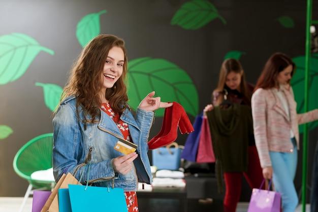 Menina sorridente segurando par de sapatos vermelhos na loja