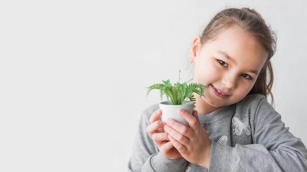Menina sorridente, segurando, planta