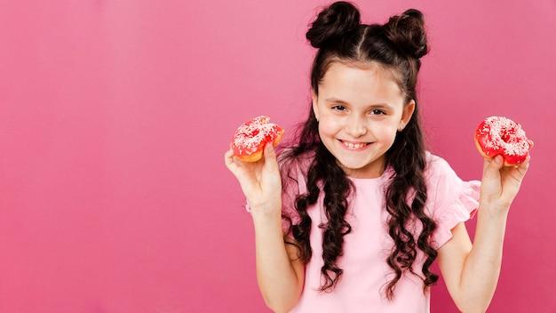 Menina sorridente segurando rosquinhas