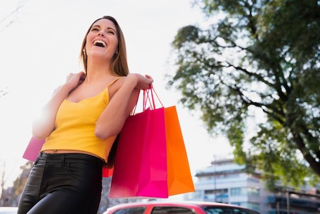 Menina sorridente segurando sacolas com árvore atrás