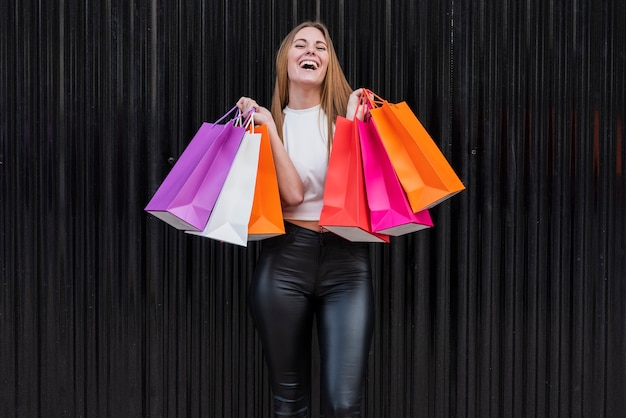Menina sorridente segurando sacolas de compras