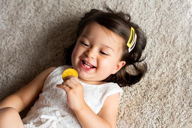 Menina sorridente segurando um bitcoin deitado no tapete