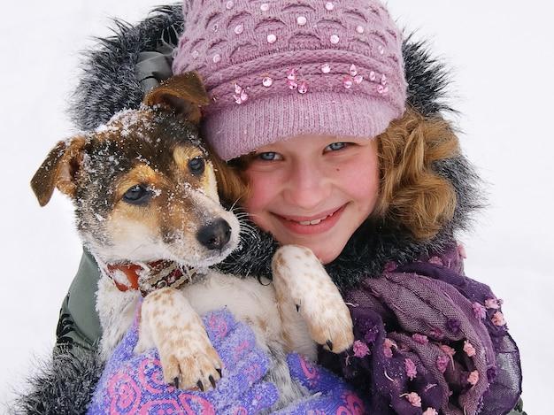 Menina sorridente segurando um cachorro, uma garota e amigos cachorrinhos, inverno, em torno de um monte de neve